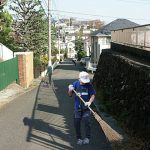 家の前を掃く男